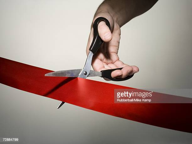 Hand cutting a red ribbon with scissors