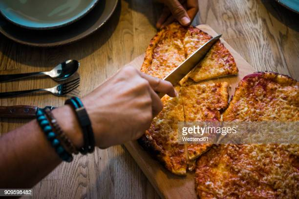 Hand cutting crispy homemade pizza with a knife