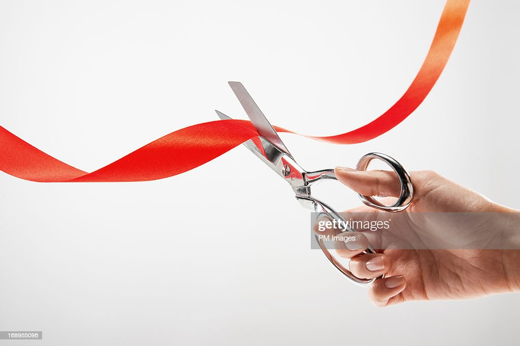 Hand cutting red ribbon with scissors : Stock Photo