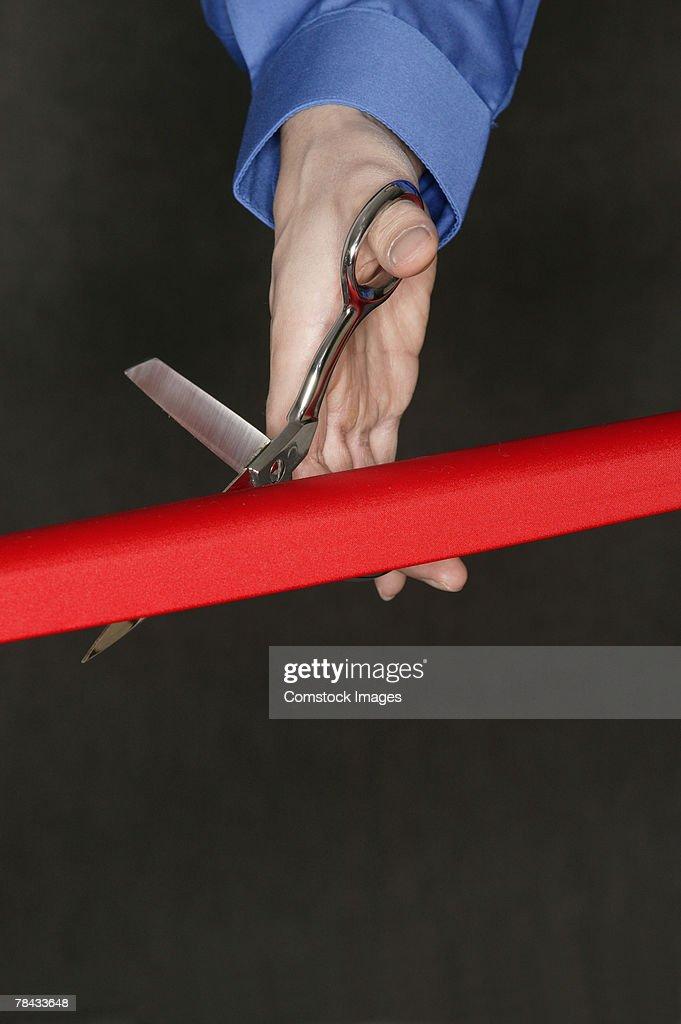 Hand cutting red tape : Stockfoto