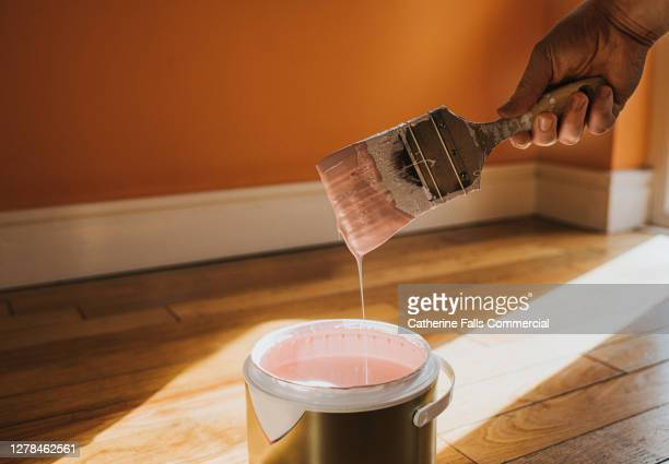 hand dipping a paint brush into a large tin of pink paint as it drips back into the pot - painting stock pictures, royalty-free photos & images