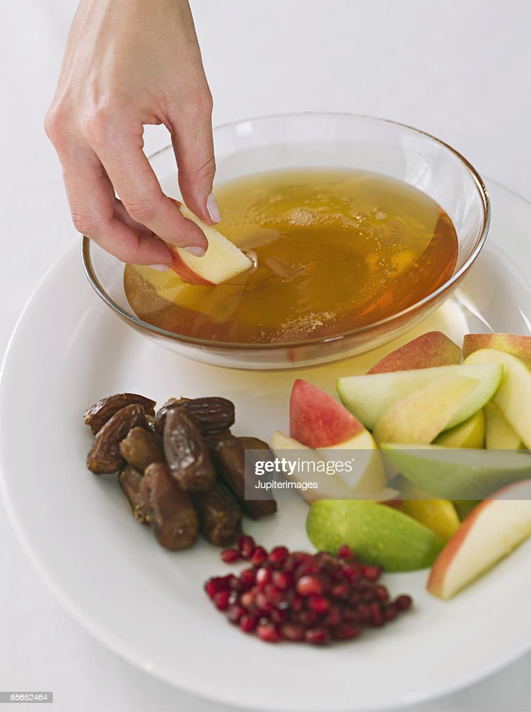 Hand dipping apple into honey with Rosh Hashanah fruit plate : Stock Photo