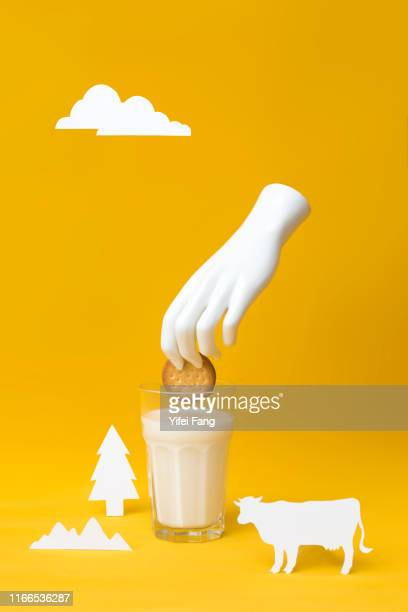 hand dipping cookie in glass of milk with farm props against color background - イラスト画法 ストックフォトと画像