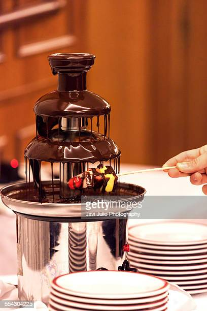 Hand dipping fruits into chocolate fondue