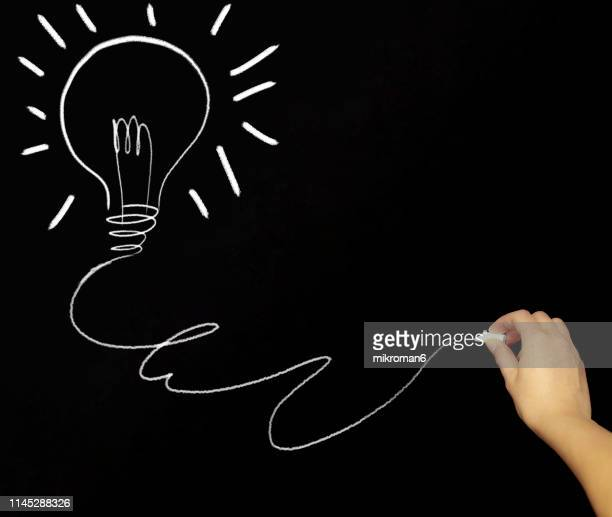 Hand drawing a light bulb with chalk in black board