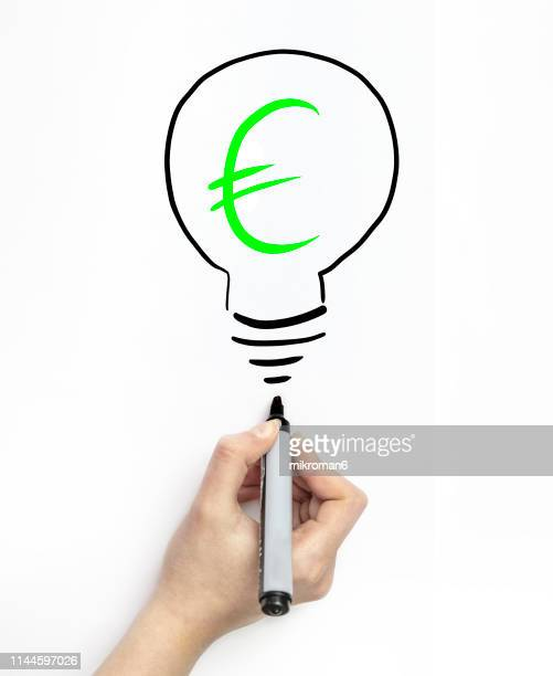 hand drawing currency in a light bulb on white page with marker - environmental signs and symbols stock pictures, royalty-free photos & images