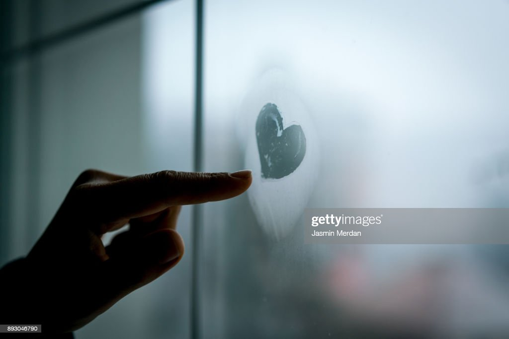 Hand drawing heart on winter window glass : Stock Photo