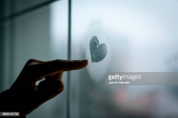 Hand drawing heart on winter window glass