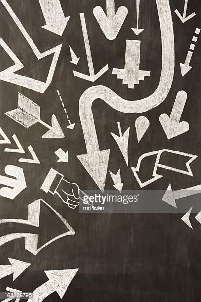 Hand drawn chalk arrows on blackboard