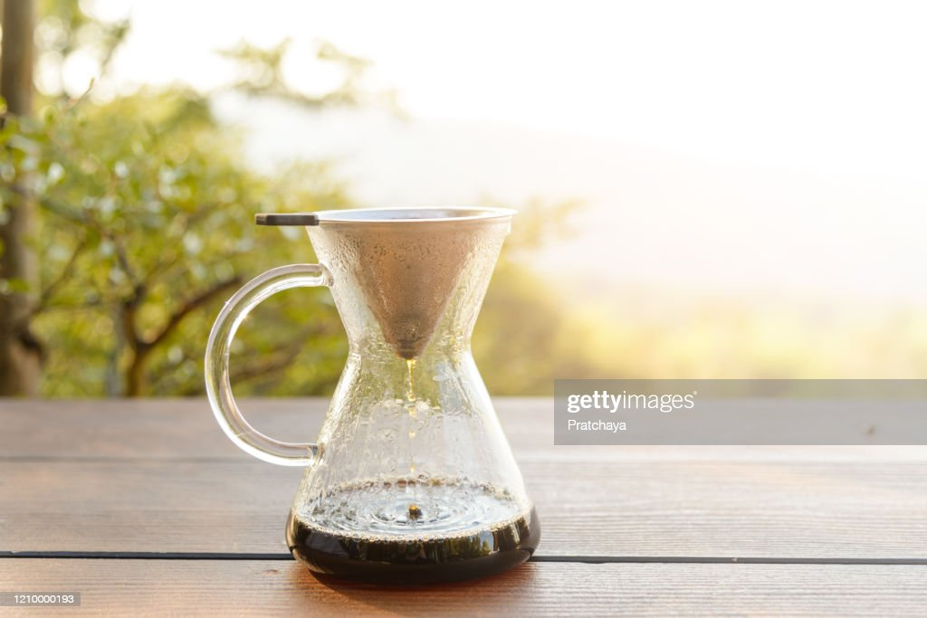 Hand drip coffee making pour over coffee with hot water being poured from a kettle with mountain view and natural green view feeling chill and relax in nature : Stock Photo