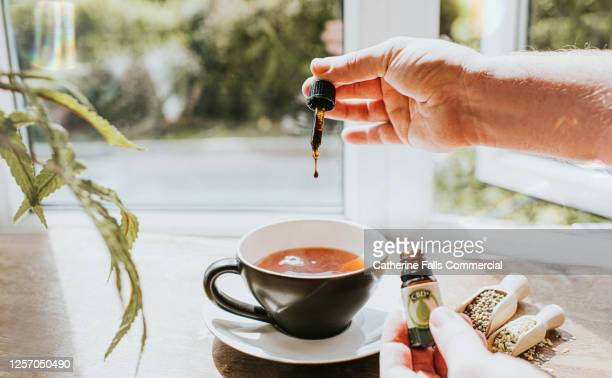 hand dropping cbd oil into a cup of tea, surrounded by cannabis plants - cbd oil stock pictures, royalty-free photos & images
