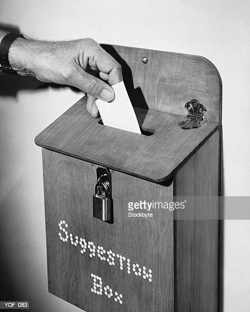 Hand dropping note in suggestion box
