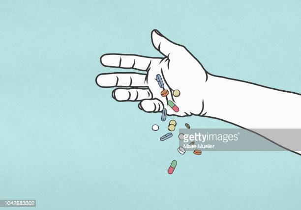 hand dropping pills on blue background - illustration stock pictures, royalty-free photos & images