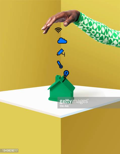 hand dropping smart home symbols onto house - human limb stock pictures, royalty-free photos & images