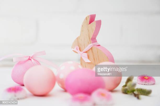 Hand dyed pink Easter eggs with bunny, daisy and catkin decoration on wooden background