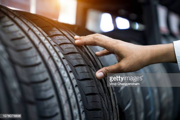 hand finger checking tire - tire stock photos and pictures