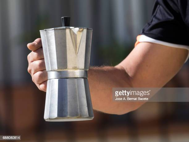 Hand from a man holding an Italian coffee machine outdoors