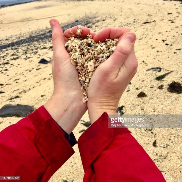 Hand full of coral beach sand in the shape of a heart