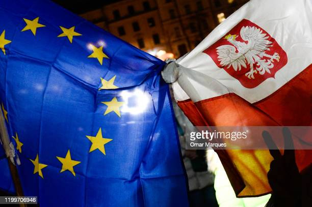 Hand gesticulates next to a Polish and European Union flag during a protest against the recently signed judiciary law by the Polish President Andrezj...