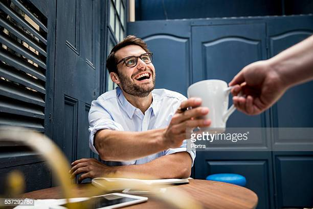 hand giving coffee to cheerful businessman - geven stockfoto's en -beelden