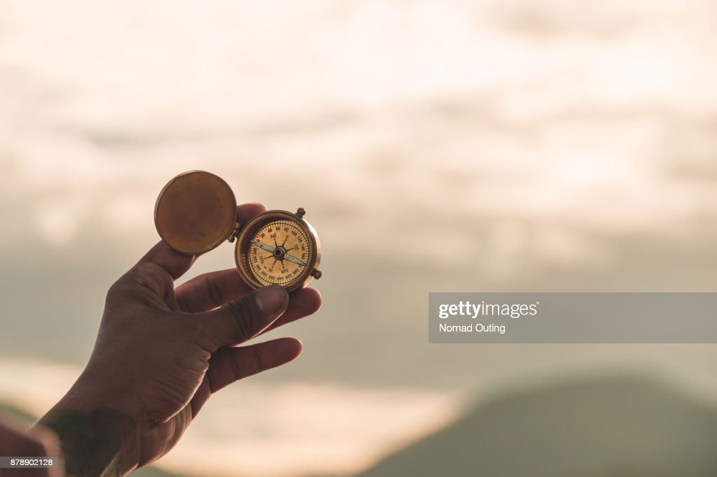hand golding compass to navigate direction,travel direction discovery