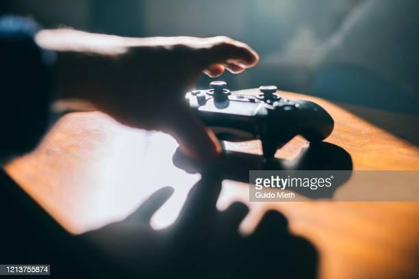 hand grabbing game pad. - ゲームコントローラー ストックフォトと画像