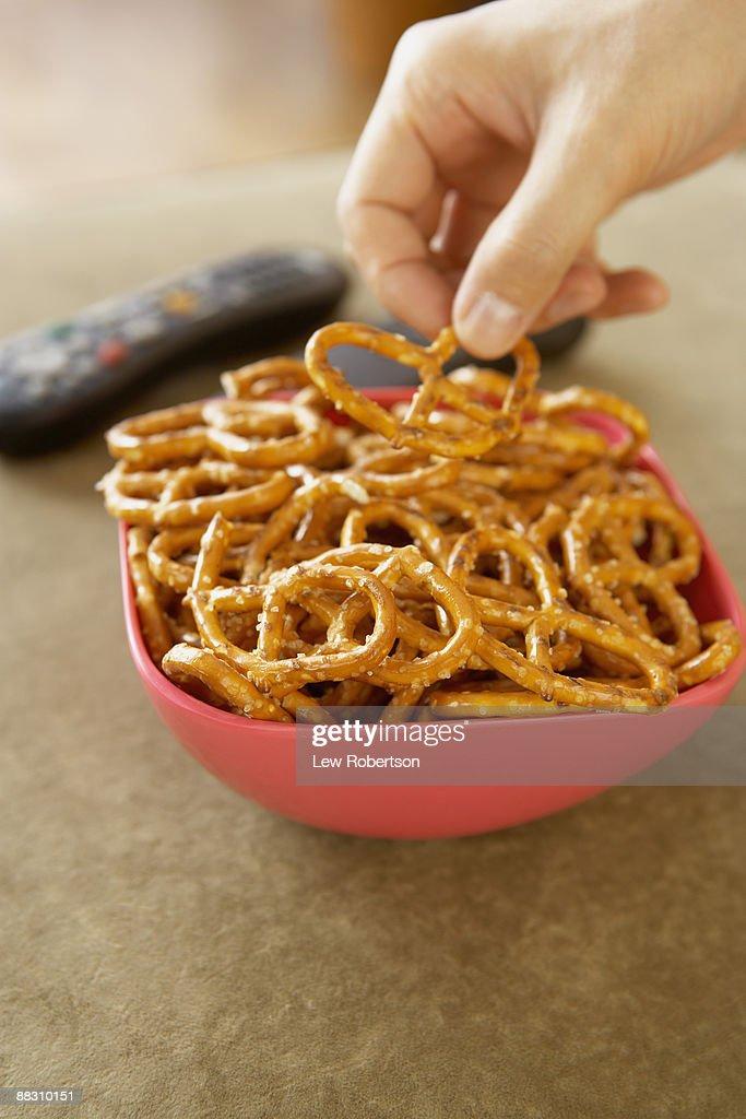 Hand grabbing pretzel out of bowl : Stock Photo