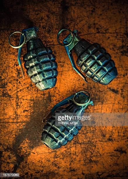 hand grenades on orange background - detonator stock photos and pictures