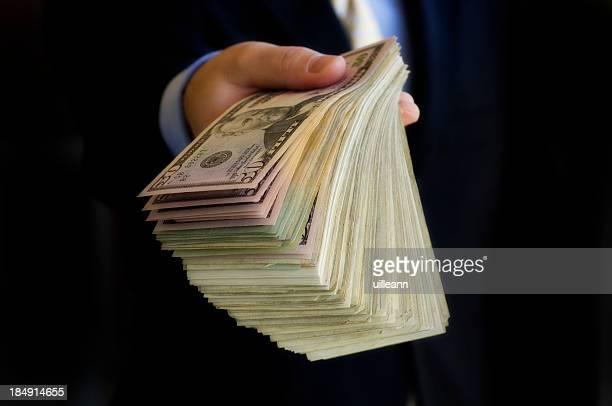 A hand handing over a wad of dollar bills
