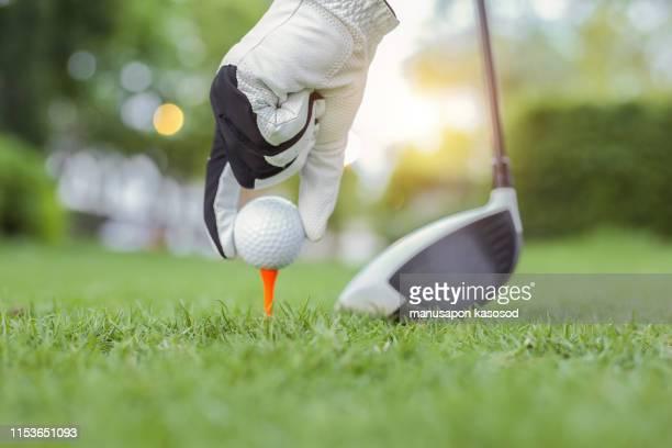 hand hold golf ball with tee on course, close-up - golfschläger stock-fotos und bilder