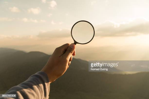 hand hold magnifying glass - detective stock pictures, royalty-free photos & images