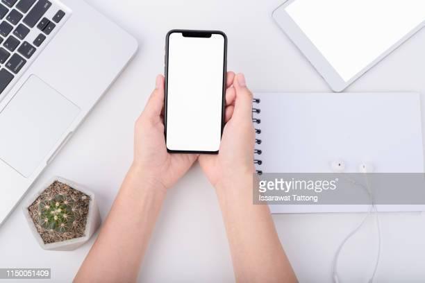 hand hold smartphone on workspace table - table top - fotografias e filmes do acervo