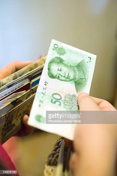 Hand holding 50 Yuan bill