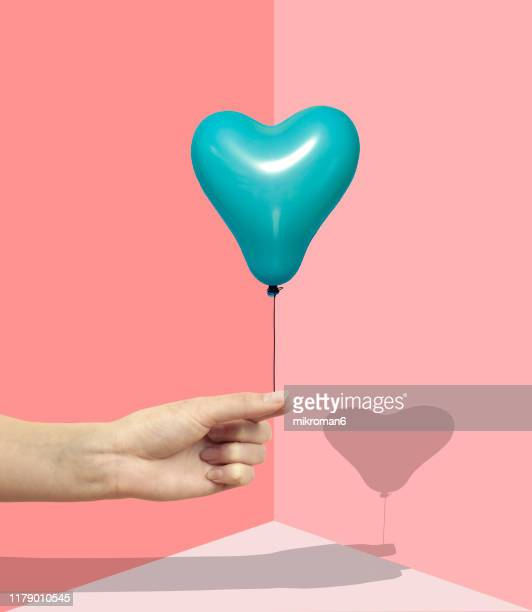hand holding a balloon with a shadow - abstract stock pictures, royalty-free photos & images