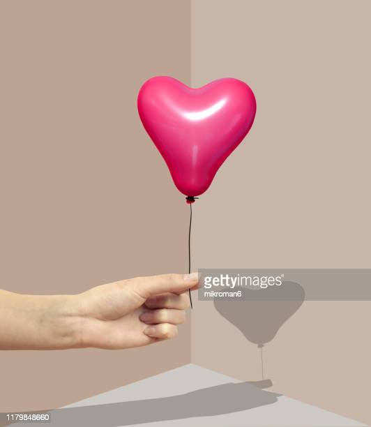 hand holding a balloon with a shadow - contemplation stock pictures, royalty-free photos & images