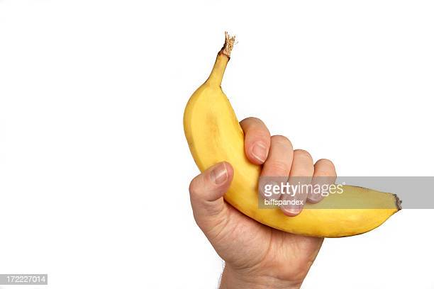 Hand holding a banana up on a white background