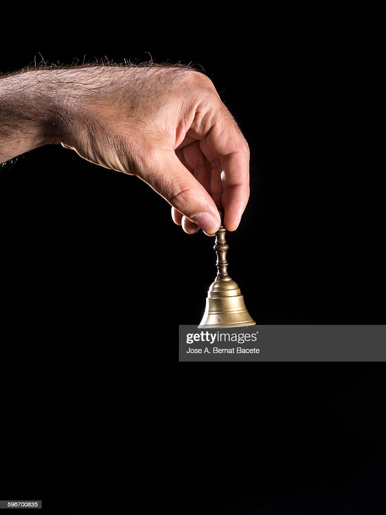 Hand holding a bell of bronze on black background : Stock Photo
