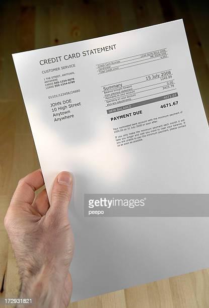 Une main tenant une facture sur une grande feuille de papier blanc.