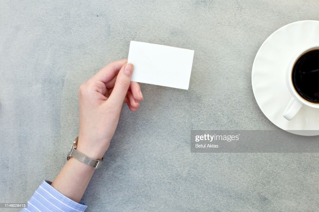 Hand holding a blank business card with coffee cup on gray background. : Stock Photo