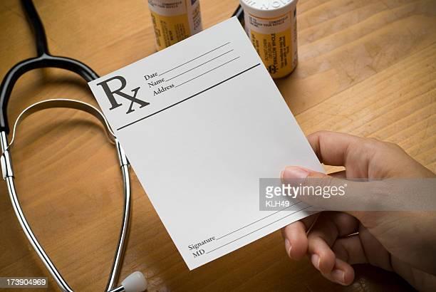 Hand holding a blank prescription.