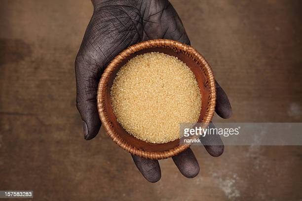 Hand Holding a Bowl with Cane Sugar