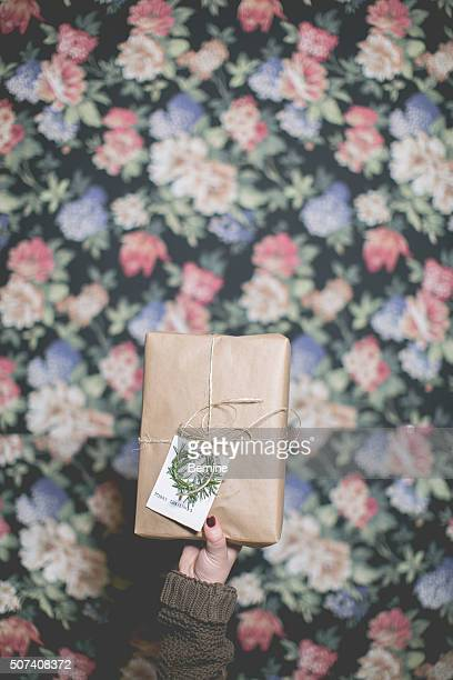 A Hand Holding a Brown Paper Christmas Present in front of Floral Wall