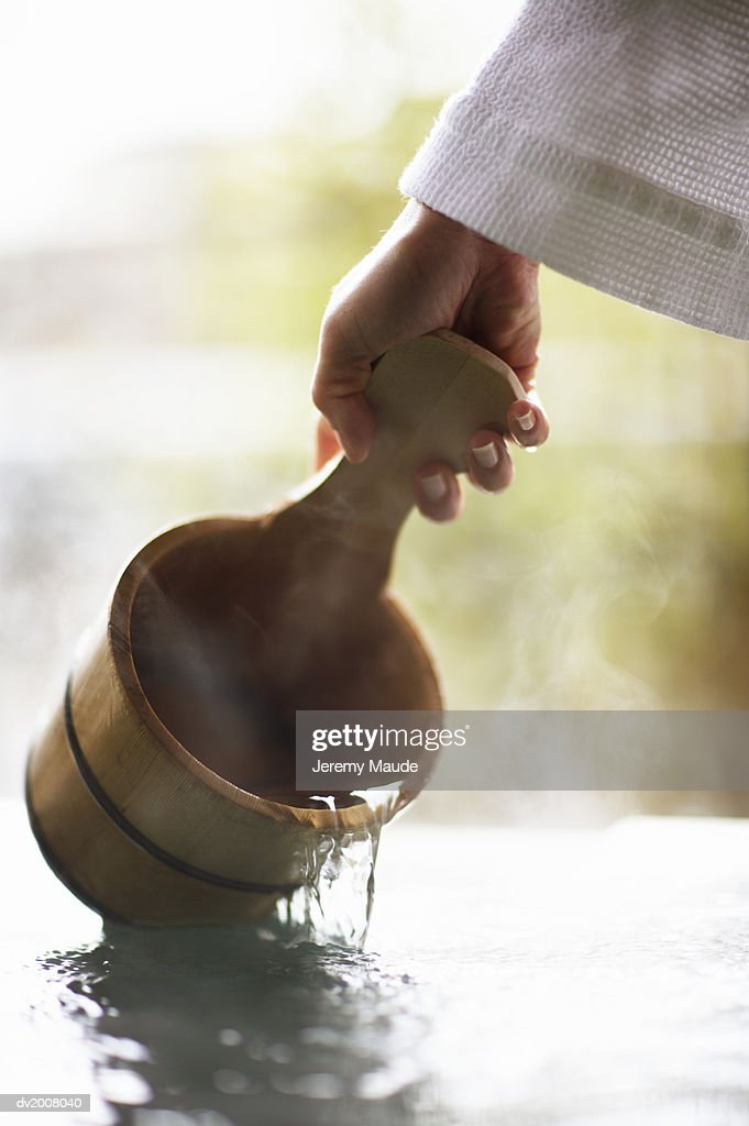 Hand Holding a Bucket Above Steamy Water : Stock Photo