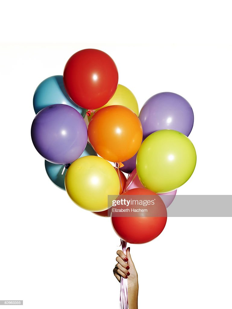 Hand holding a bunch of multi-coloured balloons : Stock Photo