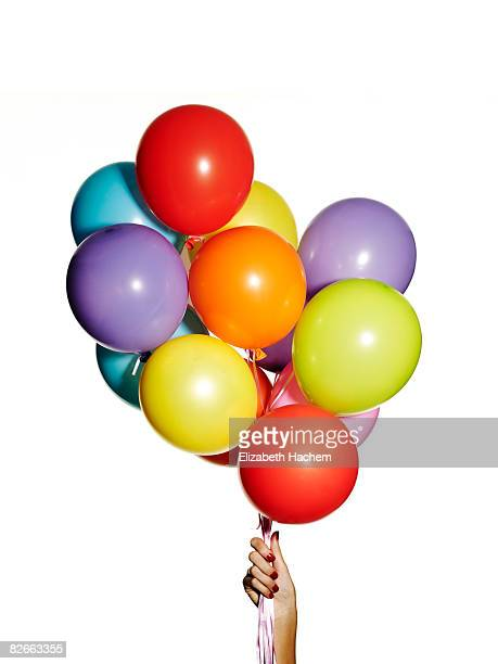Hand holding a bunch of multi-coloured balloons