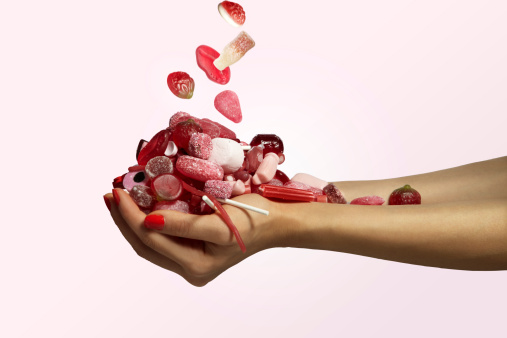 hand holding a bunch of red candy falling - gettyimageskorea