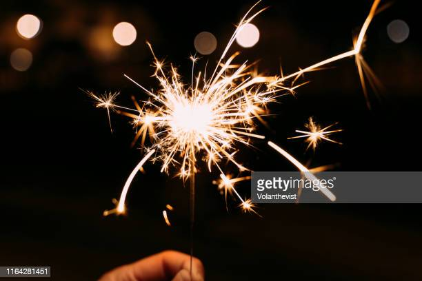 hand holding a burning sparkler at a party - sparkler stock pictures, royalty-free photos & images