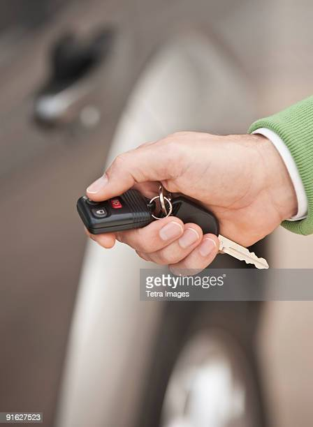 A hand holding a car remote key
