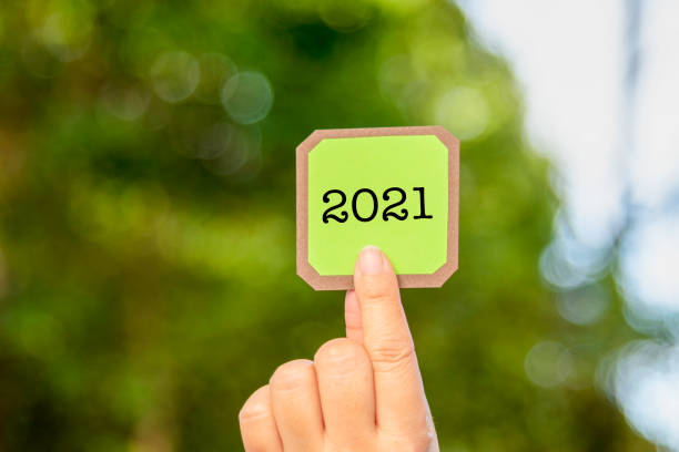 Hand Holding a Card or Labels with Year 2021 Word. Green Bokeh Background.