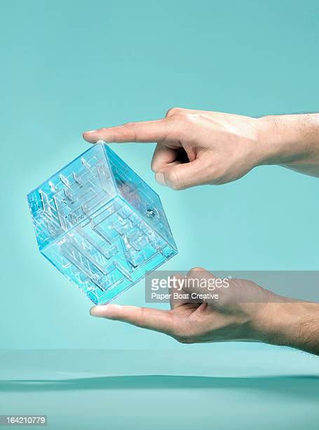 hand holding a clear glass puzzle with a maze